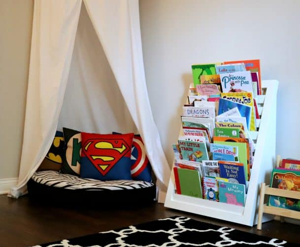 Toddler reading corner with superhero pillows in a superhero themed room.