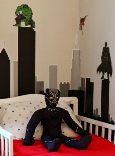 Superhero toddler bed with city skyline wall decal.